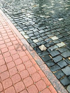 wet block sidewalk and rough cobblestone road