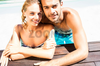 Happy couple leaning on pool edge