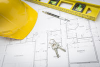 Hard Hat, Pencil, Level and Keys Resting on House Plans