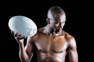 Concentrated shirtless sportsman holding rugby ball