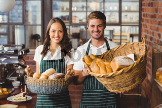 Smiling co-workers holding breads basket