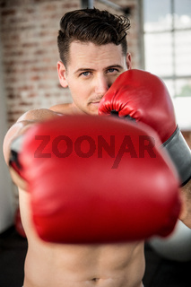 Portrait of a muscular man wearing boxing gloves