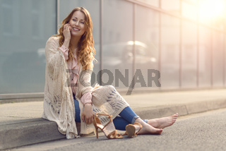 Trendy young woman sitting chatting on her mobile