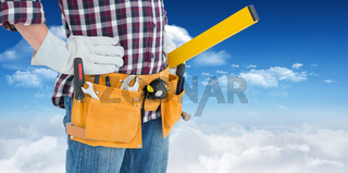 Composite image of repairman wearing tool belt while standing with hands on hips