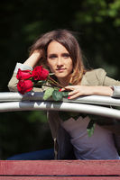 Sad young fashion woman with red roses