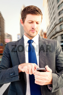 Composite image of businessman sending a text message