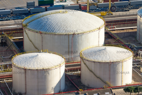 Three white storage tanks seen in a harbour