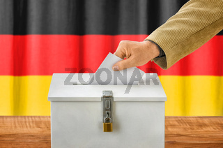 Man putting a ballot into a voting box - Germany