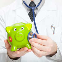 Medical doctor holding stethoscope and piggybank in hand - studio shot