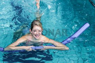 Fit woman doing aqua aerobics with foam rollers