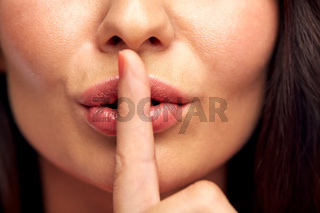 close up of young woman holding finger on lips