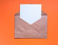 Envelop with blank letter  on orange background