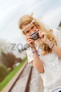 Junge Frau im Hippie-Look mit alter Kamera, steht auf Schienen