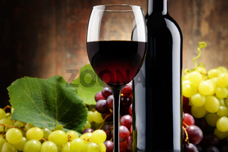 Composition with glass, bottle of red wine and fresh grapes