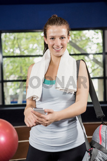Portrait of woman with a gym bag using her phone