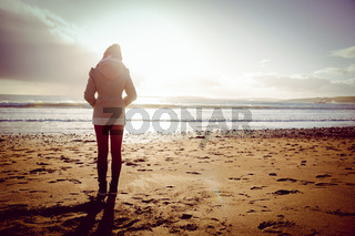 Rear view of woman looking at the sea during the sunset