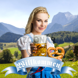 beautiful woman in a traditional bavarian dirndl with beer and pretzel in front of the alpes