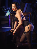 Sensual brunette with long hair in sexy lingerie and stockings posing