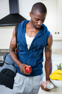 Young man carrying a gym bag, water bottle and apple