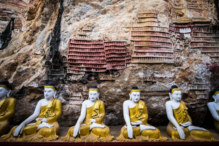 Buddhas statues and religious carving in Kaw Goon cave. Hpa-An, Myanmar