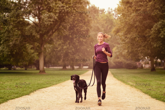 Healthy Woman Jogging in the Park with her Dog
