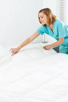 Zimmermädchen macht Bett im Seniorenheim