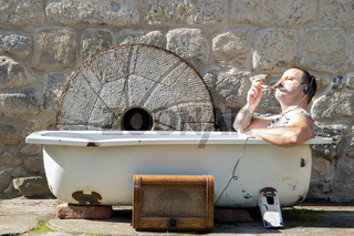 man in the bathtub smoking a pipe and listening to radio