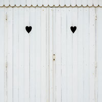 Two carved hearts on a white beach hut