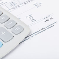 Calculator with utility bill under it - studio shot