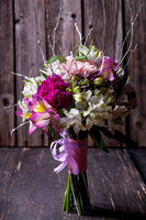 Pink bouquet from gillyflowers and alstroemeria on old wooden background