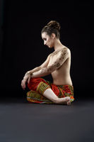 Photo of topless woman with henna patterns on body