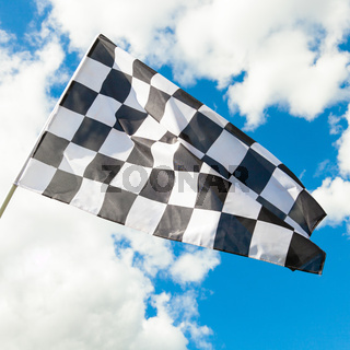 Checkered flag with blue sky and clouds on background