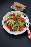 Gemischter Salat mit Roggenbrot und Besteck