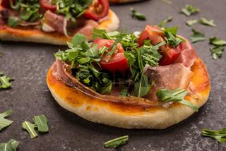 Kleine Pizza mit Schinken, Tomate und Rauke