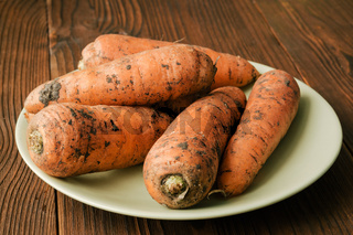 Unpeeled carrots in a green plate on a brown wooden table, close-up
