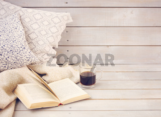 Cozy still life with book, coffee, pillows and plaid
