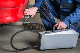 A diagnostic sensor is applied to the ehaust of a car by a mechanic, measuring the composition and substances in the exhaust fumes