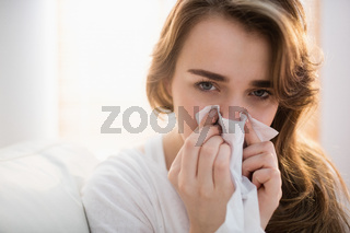 Woman blowing her nose on couch