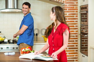 Man and woman talking together while working in kitchen