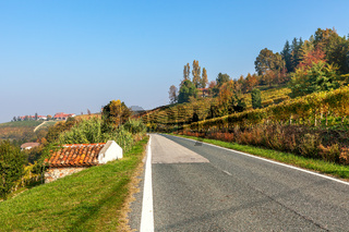 Rural road and autumnal hills in Piedmont, Italy.