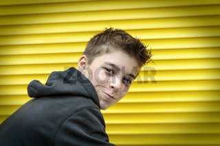 portrait of a male teenager with yellow rolling shutter in background