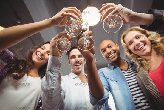 Low angle portrait of cheerful colleagues toasting in office