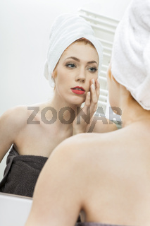 Woman From Shower Looking her Face at the Mirror