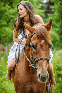young brunette woman rides a horse