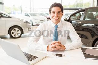 Smiling salesman behind his desk