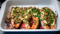 Fresh salmon fillets grilled in a pan covered with parmesan and green onion