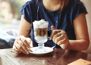 Young woman sitting in a cafe with a cup of coffee latte