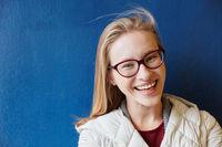 Lachende junge Frau vor blauer Wand