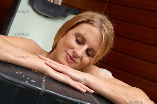 Young woman taking a bath in spa