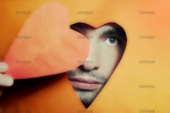 Face of young man peering from hole in heart-shaped